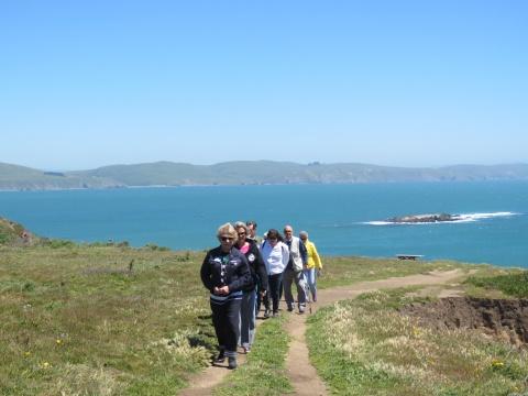 Sports Leisure travelers walk along a Bodega Bay bluff