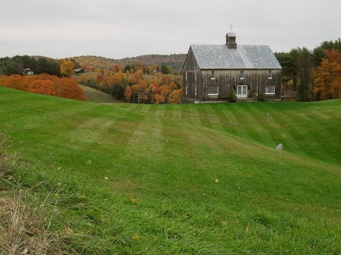 New England house on a grassy hill